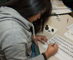 A student practices calligraphy in the Advertising Design and Commercial Art class.