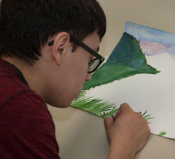 An Advertising Design and Commercial Art student creates a watercolor painting.