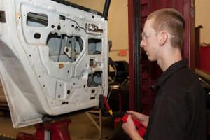student repairing a car door