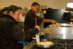 Two students cook breakfast at the stove.