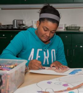 A student prepares art for a classroom bulletin board.