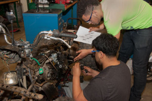 Two students repair an ATV.