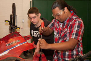 Two students work on repairing a motorcycle.