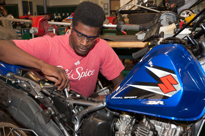 A student repairs a Suzuki motorcycle.