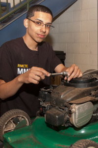 A student performs maintenance on a lawn mower.