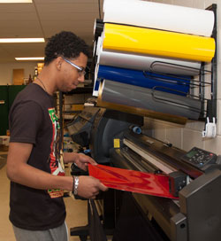 A student learns how to print on vinyl material in the Printing and Graphic Communications lab.