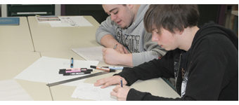 Two students work side by side in the Advertising Design and Commercial Art classroom.