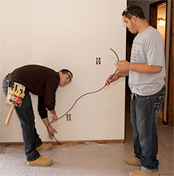 Two Electrical Technology students run coaxial cable during a house renovation project.