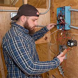 An Electrical Technology student checks his wiring with the use of a voltage meter.