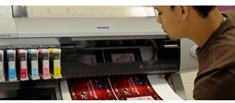 A student checks the output of a digital printer.