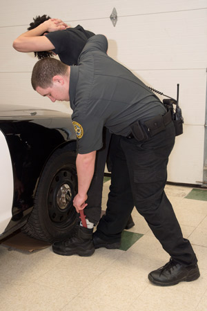 A PSS student simulates apprehending a crime suspect