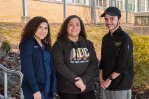 Three RMCTC students pose for a photo in front of the school.